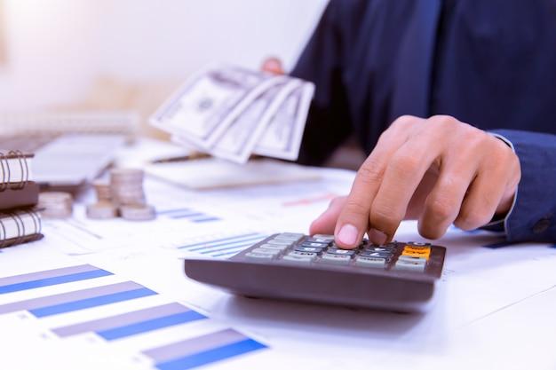 Mittelteil des geschäftsmannes calcuting tax using calculator in office.