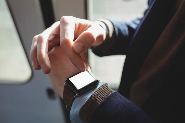 Mittelteil des geschäftsmannes, der smartwatch auf reisen verwendet