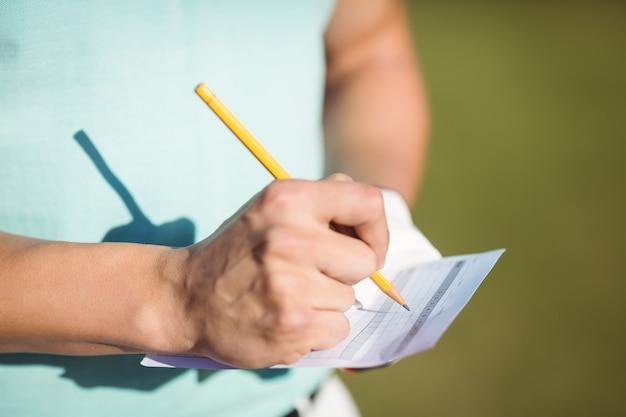 Mittelteil des golfers mit scorekarte