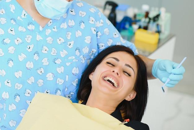 Mittelteil des männlichen zahnarztes, der die schürze bei der patientin vor der behandlung in der klinik anpasst