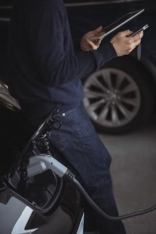 Mittelteil des mannes, der digitales tablet und mobiltelefon beim laden des elektroautos verwendet