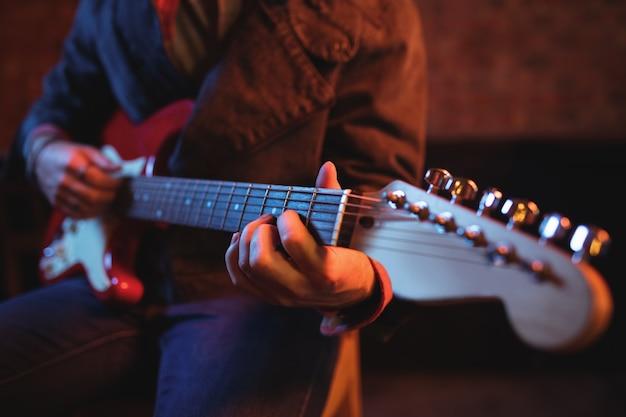 Mittelteil des mannes, der gitarre spielt