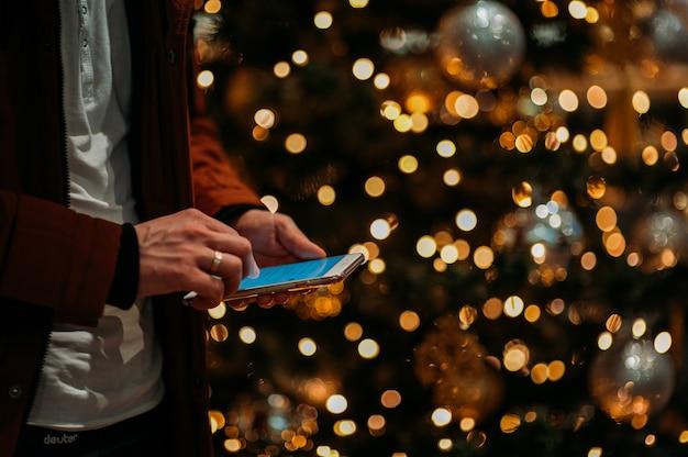 Mittelteil des mannes, der intelligentes telefon gegen belichteten weihnachtsbaum verwendet.