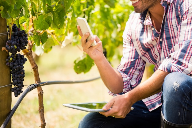 Mittelteil des mannes, der telefon beim halten der tablette verwendet