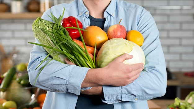 Mittelteil des mannes rohes gemüse zu hause halten