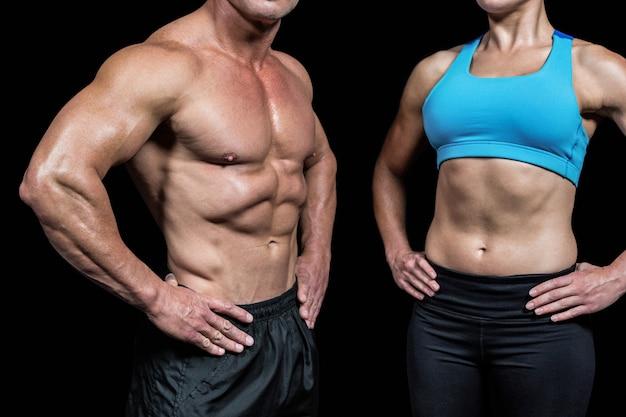 Mittelteil des muskulösen mannes und der frau mit den händen auf hüfte gegen schwarzen hintergrund