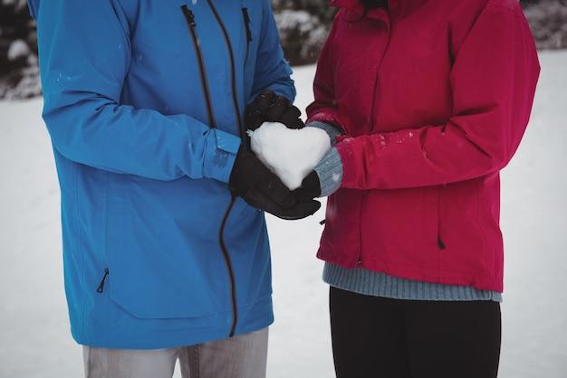 Mittelteil des paares in warmer kleidung, die schneebedecktes herz hält