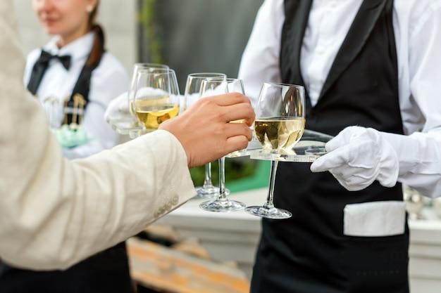 Mittelteil des professionellen kellners in uniform, der wein während der buffet-catering-party, der festlichen veranstaltung oder der hochzeit serviert. volle gläser champagner auf tablett. party-catering im freien, kellner im dienst.