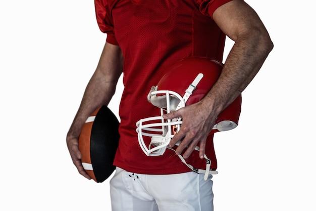 Mittelteil des spielers rugbyball und -helm halten