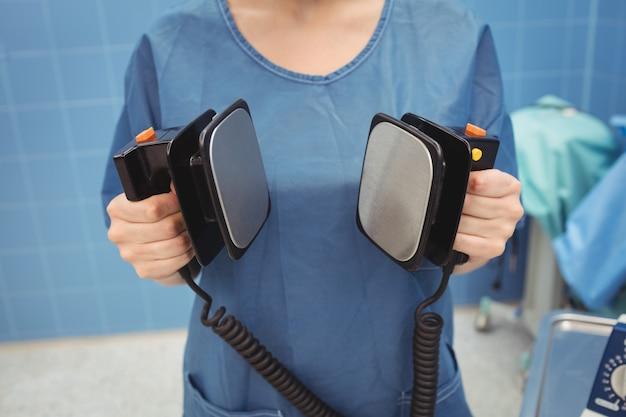 Mittelteil des weiblichen chirurgen, der den defibrillator hält