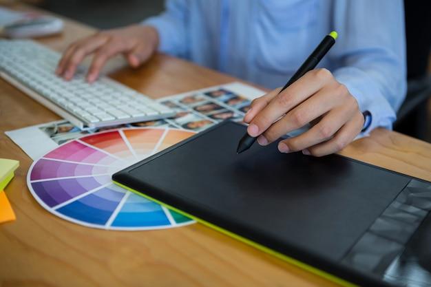 Mittelteil des weiblichen grafikdesigners unter verwendung des grafiktabletts am schreibtisch