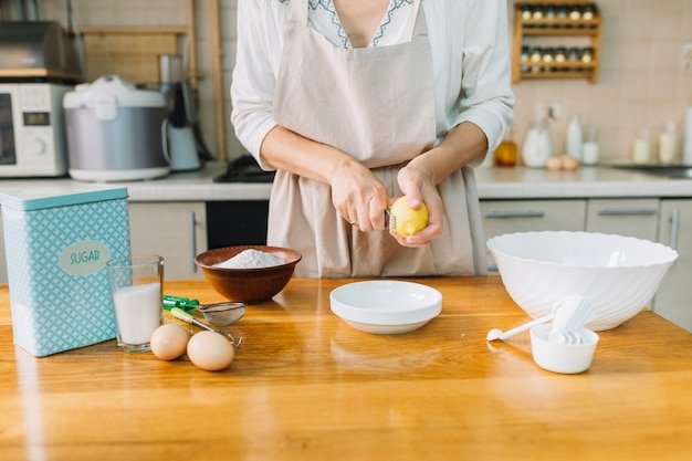 Mittelteil einer frau, die zitrone beim vorbereiten des kuchens zerreibt