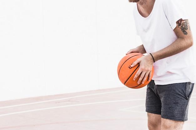 Mittelteilansicht der hand eines männlichen spielers, die basketball hält