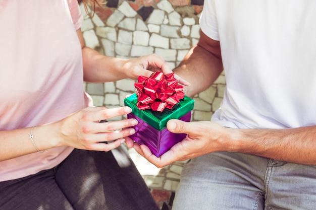 Mittelteilansicht der hand eines paares, die geschenkbox hält