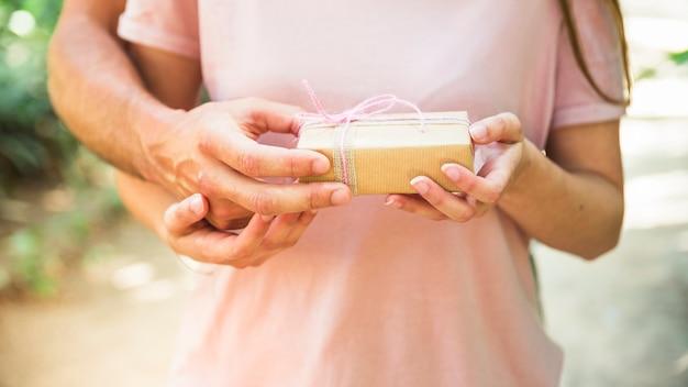 Mittelteilansicht der hand eines paares, die kleine valentinsgrußgeschenkbox hält