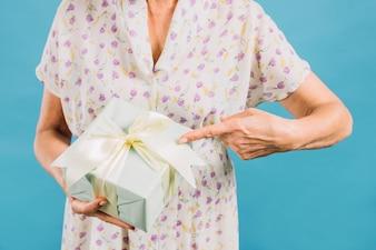 Mittelteilansicht einer Frau, die auf Geburtstagsgeschenk zeigt