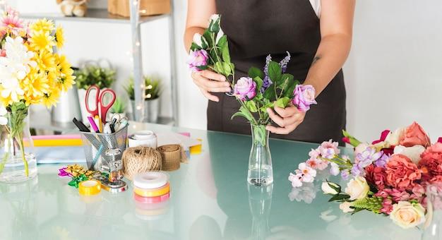 Mittelteilansicht einer sortierenden blumen der frau hand im vase auf schreibtisch