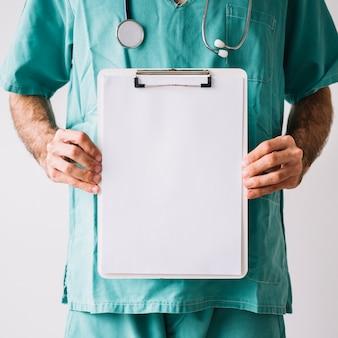Mittelteilansicht eines männlichen Doktors, der Klemmbrett mit leeren Weißbüchern hält