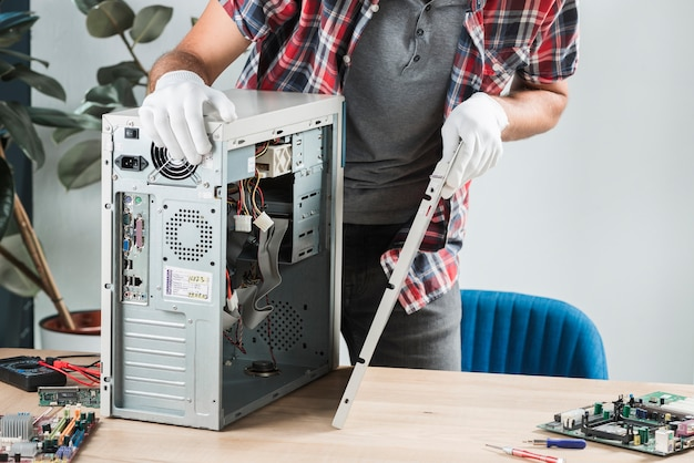 Mittelteilansicht eines montierenden computers des männlichen technikers auf hölzernem schreibtisch