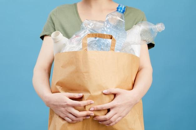 Mittelteilporträt der nicht erkennbaren frau, die papiertüte mit plastikflaschen hält, während sie isoliert stehen