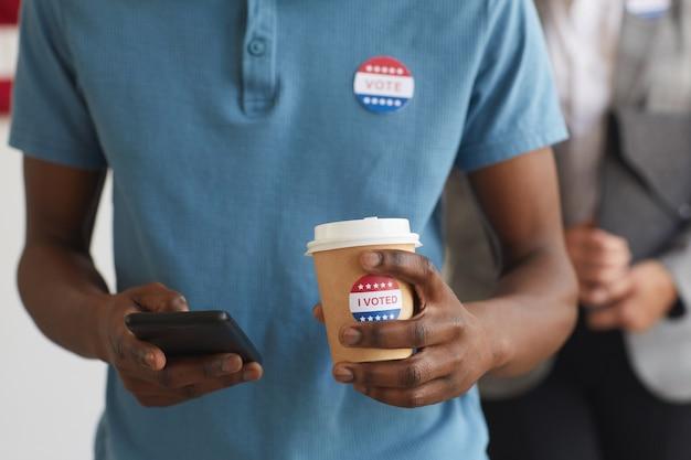 Mittelteilporträt des jungen afroamerikanischen mannes mit i voted-aufkleber, der am wahltag im wahllokal steht, kopienraum