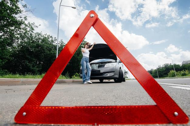 Mitten auf der autobahn steht ein junges mädchen neben einem kaputten auto und ruft am telefon um hilfe. ausfall und panne des autos. warten auf hilfe.