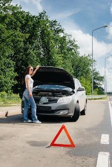 Mitten auf der autobahn steht ein junges mädchen neben einem kaputten auto und schaut unter die motorhaube. ausfall und panne des autos. warten auf hilfe.