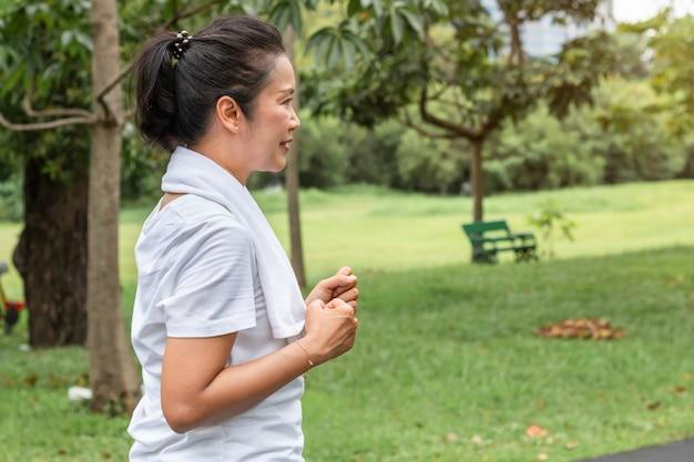 Mittlere asiatische greisin, die im park lächelt und rüttelt.