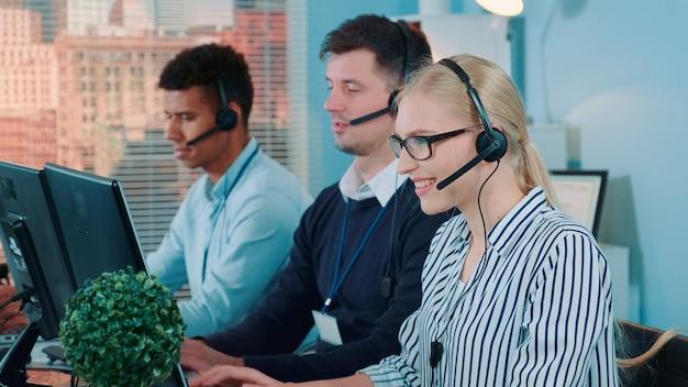 Mittlere aufnahme des weiblichen kundenservice, der in einem geschäftigen callcenter arbeitet, indem sie mit dem internationalen ...