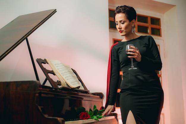 Mittlere aufnahme einer attraktiven und modischen frau, die die klaviertastatur berührt und weinglas hält holding