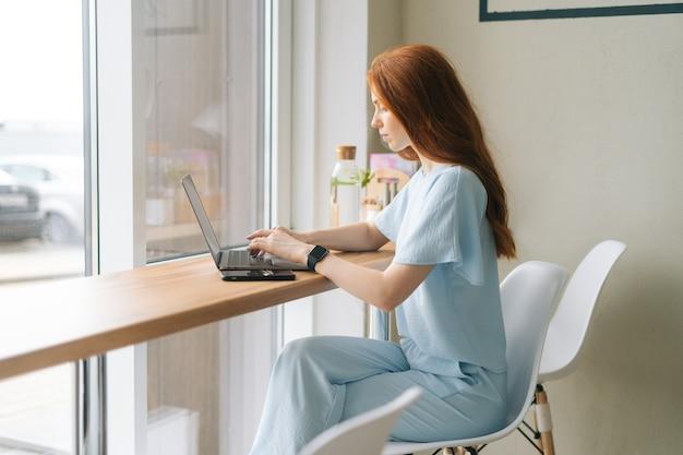 Mittlere aufnahme einer fokussierten jungen frau, die auf einem laptop am tisch am fenster im café sitzt und auf den bildschirm schaut. hübsche kaukasische dame der rothaarigen entfernt, die arbeitet oder studiert.