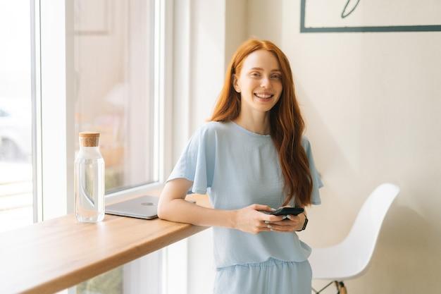 Mittlere aufnahme einer lächelnden, charmanten jungen frau mit handy, die online-nachrichten am fenster in einem gemütlichen hellen café eingibt. kaukasische dame der hübschen rothaarigen, die freizeitbeschäftigung im café hat.