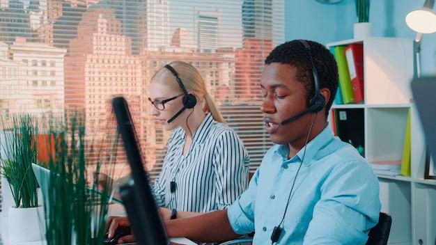 Mittlere aufnahme eines freundlichen afrikanischen mannes, der im callcenter arbeitet und internationale anrufe mit einem headset beantwortet