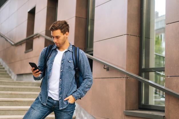 Mittlere aufnahme eines gutaussehenden liefermannes mit großem thermorucksack, der das telefon hält, auf den bildschirm schaut und die navigations-app verwendet. kuriermännchen, das die bestellung auf der treppe des bürogebäudes erhält.
