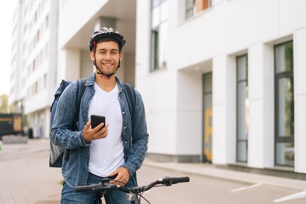 Mittlere aufnahme eines lächelnden, gutaussehenden männlichen kuriers mit thermorucksack, der mit fahrrad in der stadtstraße steht und die navigations-app am telefon verwendet. lieferbote, der nach der kundenadresse sucht, die smartphone sucht.