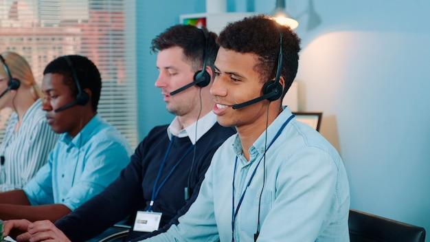 Mittlere aufnahme eines schwarzen call-center-agenten, der sich nach einem telefonanruf mit dem...