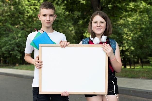 Mittlere aufnahme gymnasiasten halten whiteboard