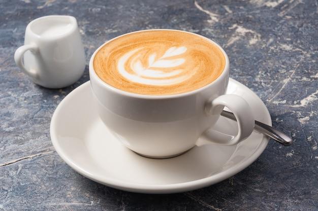Mittlere cappuccino-tasse auf grauem hintergrund
