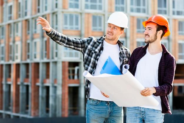 Mittlere einstellung des architekten und ingenieurs, die den bau überwachen