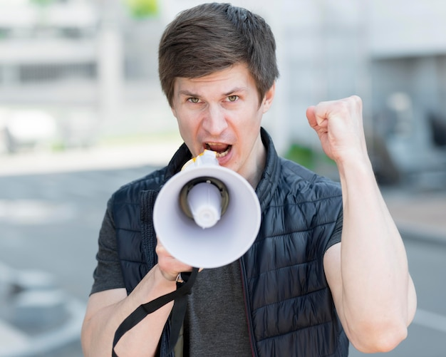 Mittlere einstellung eines mannes mit megaphon, der auf der straße protestiert