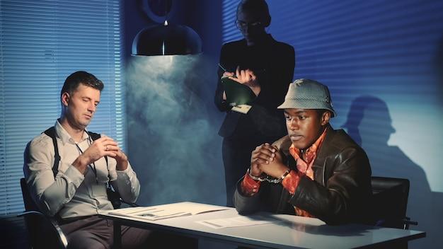 Mittlere einstellung eines schwarzen gefangenen in handschellen, der ein interview mit einem kaukasischen detektiv im verhörraum geführt hat