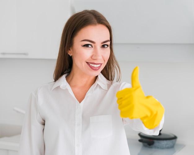 Mittlere einstellung von frau und daumen hoch mit handschuhen
