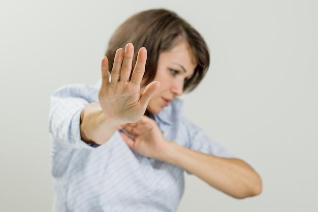 Mittlere erwachsene emotionale frau, die stoppschild zeigt.
