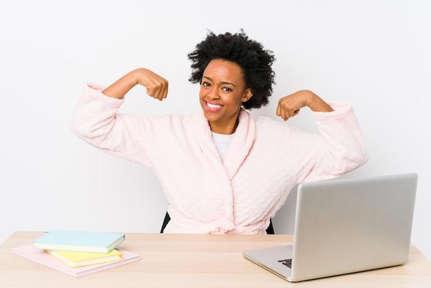Mittlere gealterte afroamerikanerfrau, die zu hause arbeitet, stärkegeste mit den armen zeigend