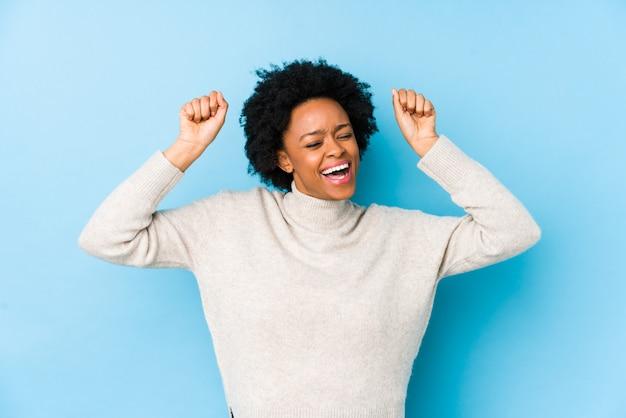 Mittlere gealterte afroamerikanerfrau gegen eine blaue wand trennte das feiern eines speziellen tages, springt und hebt arme mit energie an.