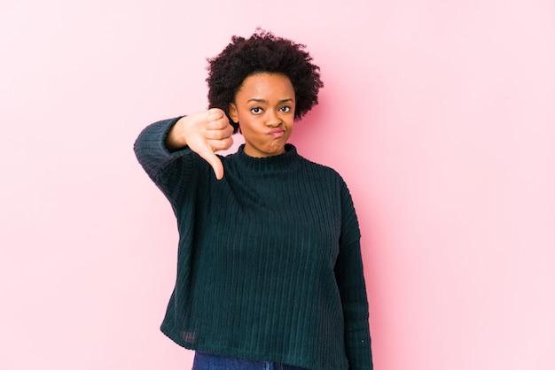 Mittlere gealterte afroamerikanerfrau gegen eine rosa wand lokalisiert, eine abneigungsgeste, daumen unten zeigend. uneinigkeit konzept.