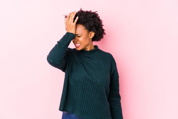 Mittlere gealterte afroamerikanerfrau gegen eine rosa wand lokalisierte das vergessen etwas und schlug stirn mit palme und schließend augen.