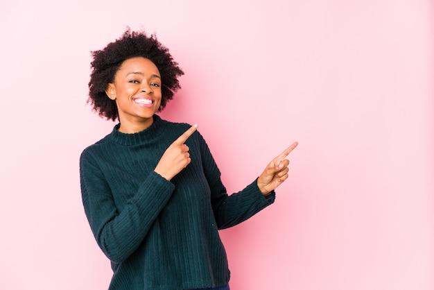 Mittlere gealterte afroamerikanerfrau gegen eine rosa wand lokalisierte das zeigen mit den zeigefingern auf einen kopienraum und drückte aufregung und wunsch aus.