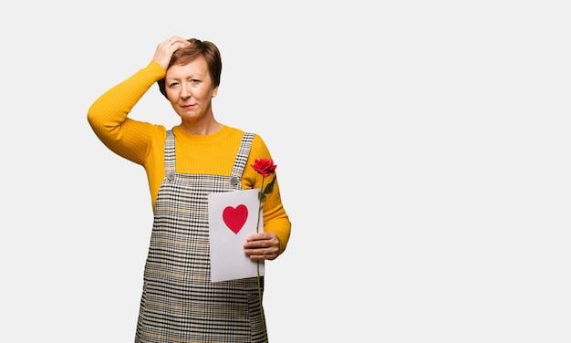 Mittlere gealterte frau, die den valentinsgrußtag besorgt besorgt und überwältigt
