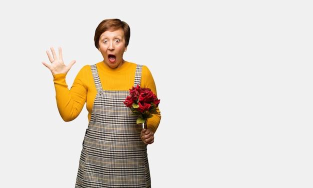 Mittlere gealterte frau, die den valentinsgrußtag feiert einen sieg oder einen erfolg feiert